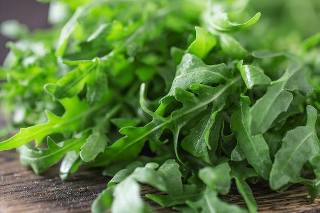 テーブルの上のボウルに新鮮な緑のルッコラ。サラダ用ルッコラ