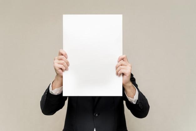 スーツを着た男が彼の前に白いシートを持っています。ポスターの後ろに隠れている男。白いパターンコピースペースの顔の男
