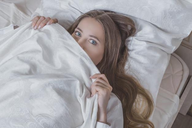ベッドの準備をしてベッドの上の美しい少女