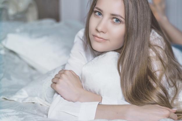 ランジェリーのベッドの上の美しい若い女性