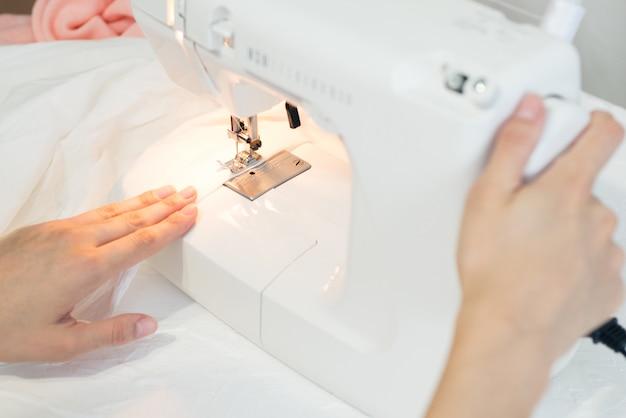 白い布を縫う服、ミシンに手を縫うプロセス