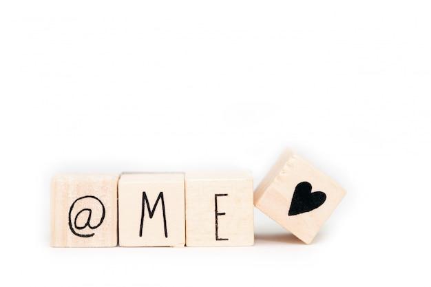 Деревянные кубики со знаком «а», словом «я» и символом сердца на белом фоне