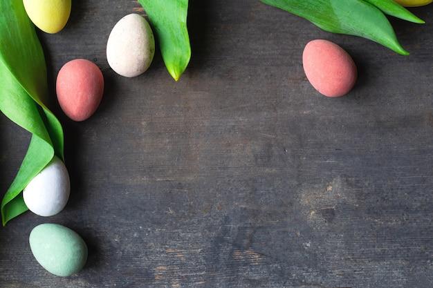 Окрашенные красочные пасхальные яйца на старинной деревянной фоновой текстуре, мягкие пастели и зеленые листья современного дизайна