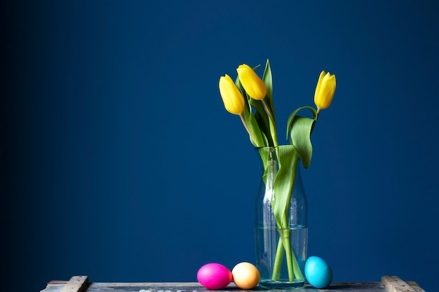 ガラスの花瓶の柔らかいパステルと新鮮な黄色のチューリップと青い壁の近くのヴィンテージの木製の棚のテクスチャにカラフルなイースターエッグを染め、緑の葉のモダンなデザイン