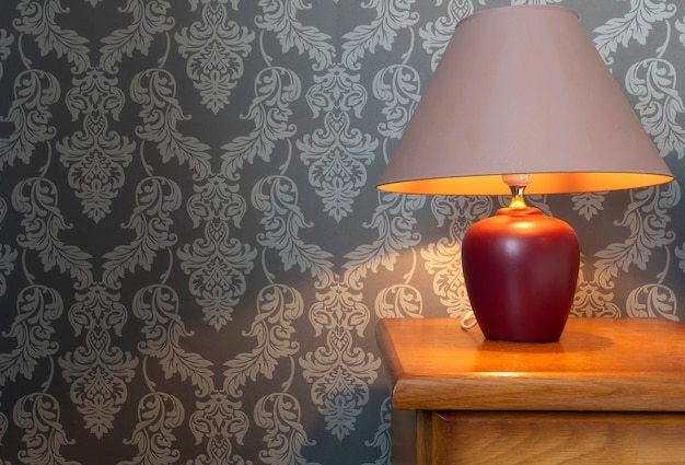 白いシーツと居心地の良いランプ、パターンの壁紙のレトロなデザインの木製ベッドのクローズアップ。