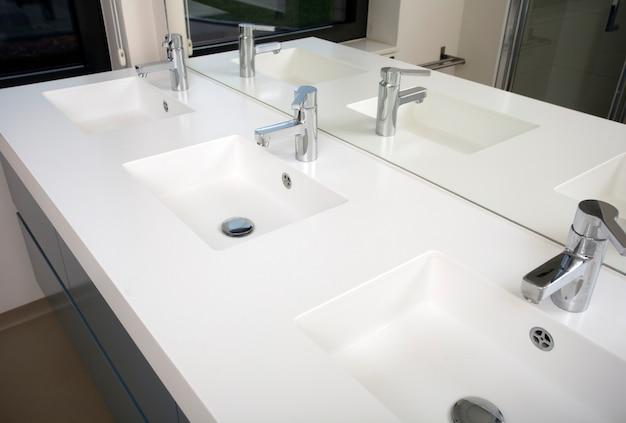 Три раковины для ванной комнаты с тремя раковинами и тремя раковинами белого цвета с современным дизайном и зеркалом