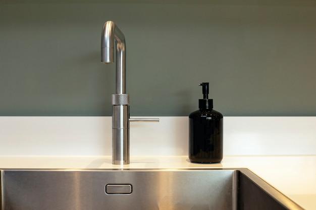 Пустая чистая кухонная раковина и дозатор мыла современного дизайна с серой стеной