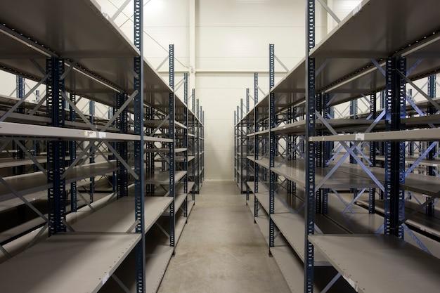 モダンなデザインの収納用に空のラックが入った巨大な倉庫、流通用の金属製の棚