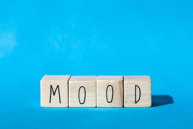 青い背景、感情の概念と気分という言葉で木製キューブ