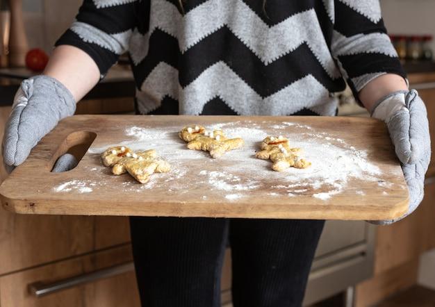 キッチンで自家製ジンジャーブレッドマンクッキーのベーキングトレイを保持している女性の手