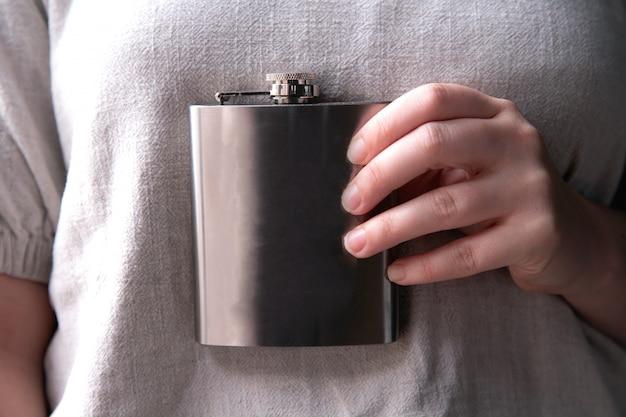 酒、アルコール、ドリンクのコンセプトのクローズアップのステンレスヒップフラスコを持っている手
