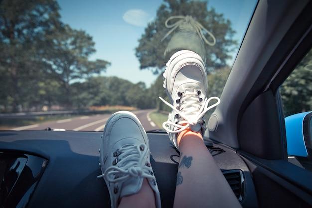 自由車旅行のコンセプト-白いスニーカーを身に着けているダッシュボードに足でリラックスした女性。