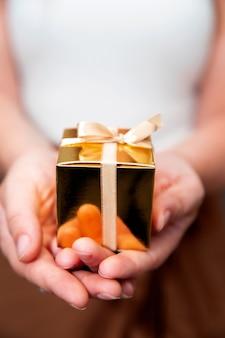 Женские руки держат золотую подарочную коробку