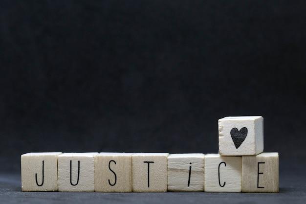 黒い背景に正義という言葉で木製キューブ、黒の生活問題の概念