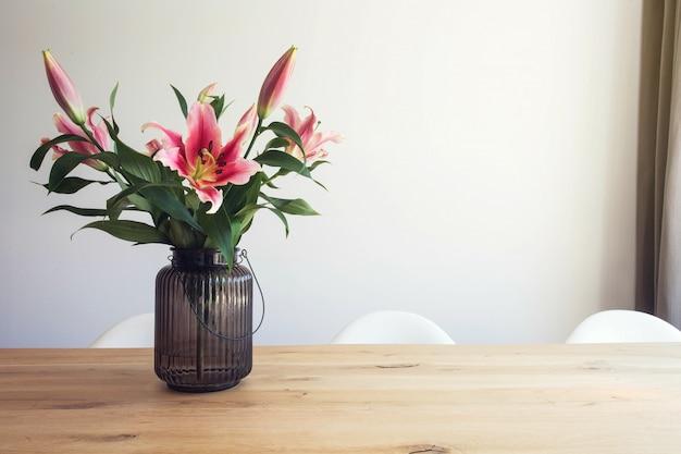 Розовая лилия цветы в вазе на деревянном столе в интерьере на белой стене в современной комнате