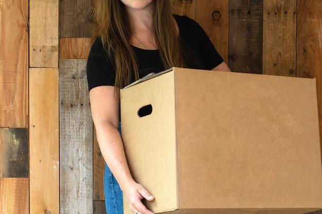 Счастливая молодая женщина, несущая картонную коробку для перемещения для своего нового дома, переезда или нового дома, концепция хрупкого и ретро