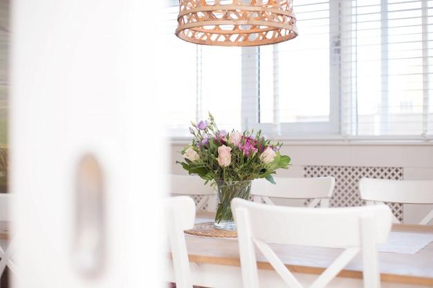 モダンな家のクローズアップの白い部屋で花の装飾と居心地の良いダイニングルームのインテリア