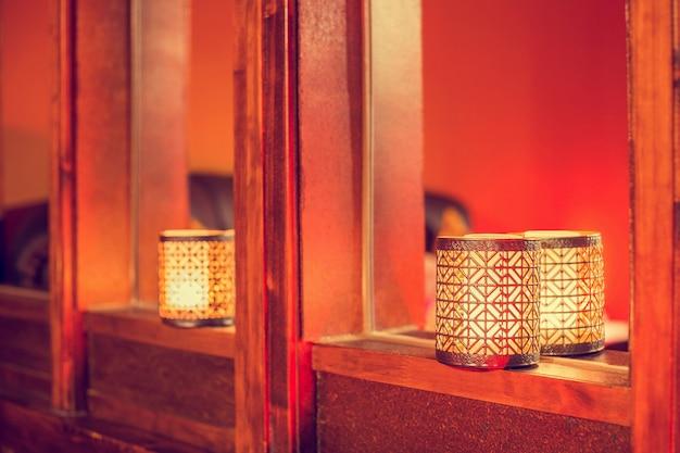 木材、カラフルなアラビア語テクスチャ暗い背景に東洋のキャンドル。