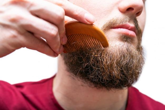 Молодой человек с расческой чистит бороду и усы на белом