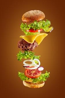 白い背景の上の食材を飛んで大きなおいしい自家製ハンバーガー。分離されました。