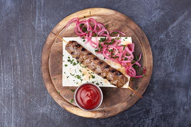 Луля кебаб с красным луком и салатом, традиционное кавказское блюдо.