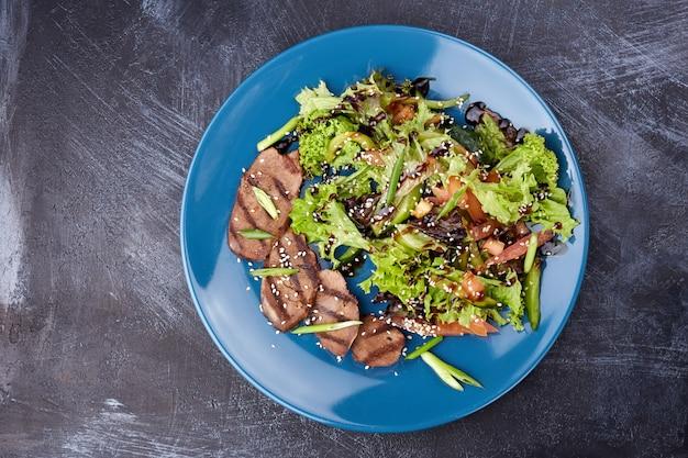 子牛のサラダ、レタス、リンゴ、梨、暗い背景の木に青い皿にトマト