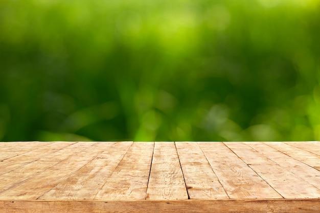 葉の背景のボケ味を持つ空の木製デッキテーブル。製品表示モンタージュの準備ができています。
