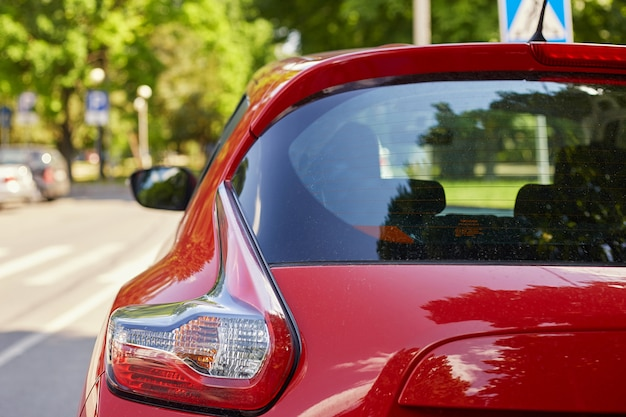 Заднее окно красного автомобиля припарковало на улице в дне лета солнечном, вид сзади. макет для наклейки или наклейки