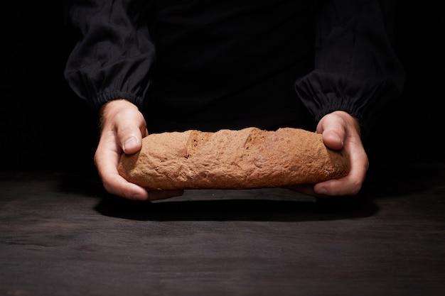 Бейкер мужчина держит красивый круглый хлеб