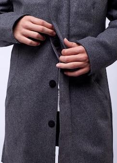 Молодой красавец в сером зимнем пальто изолирован на белом