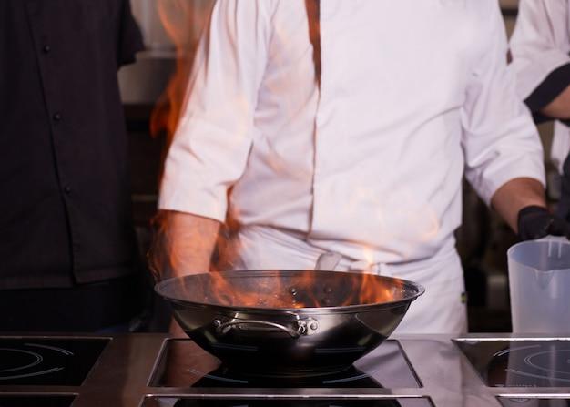 キッチンストーブのフライパンで炎で調理するシェフ。