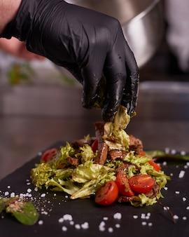 Процесс приготовления теплого салата с телятиной. руки шеф-повара в черных перчатках. черная грифельная доска.
