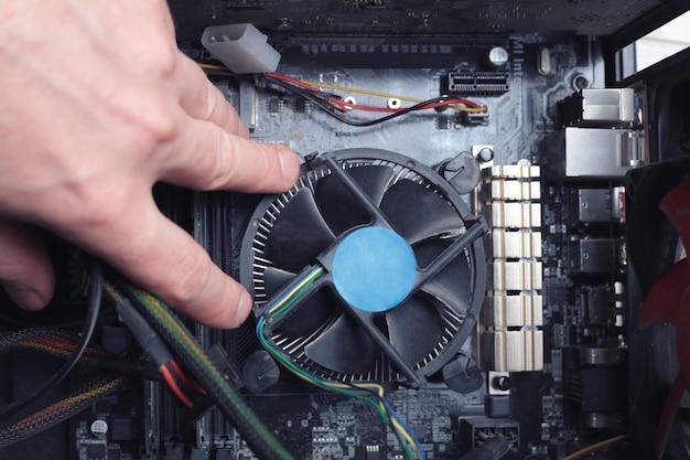 Человек ремонтирует компьютерный кулер.