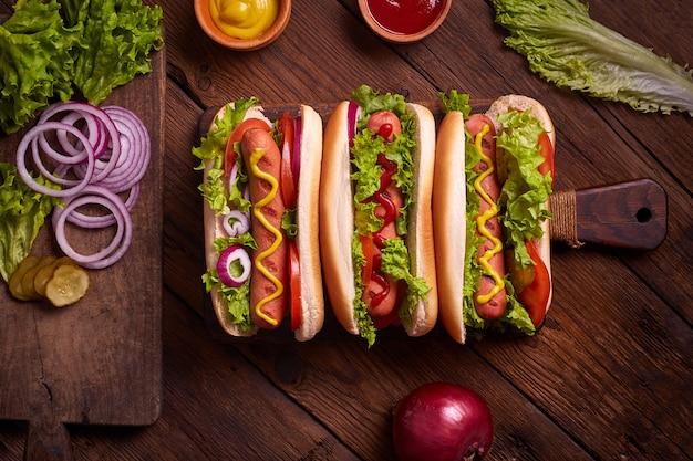 ホットドッグ。マスタードとケチャップのピクニック木製テーブルで焼きホットドッグ。サンドイッチ