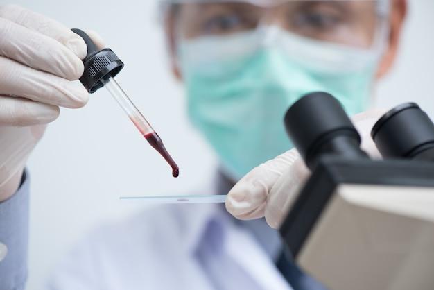 Техник или врач, исследующий микроскоп образца крови