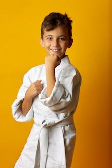Веселый мальчик в белом кимоно улыбается