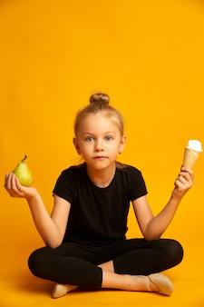 梨とアイスクリームの間で選択する困惑した小さなダンサー