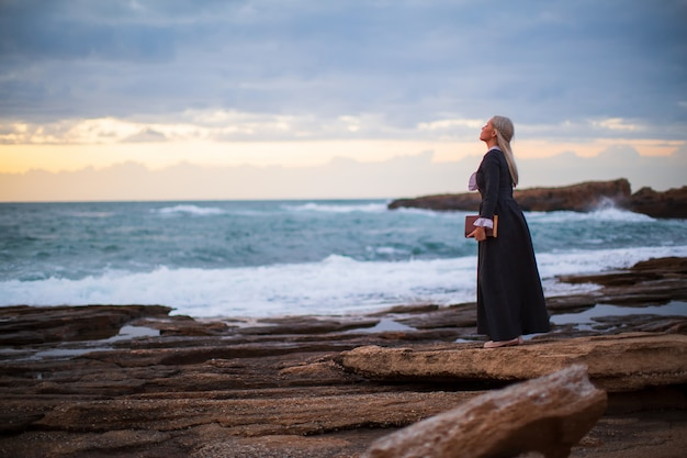 Романтичная молодая красивая дама смотрит на закат с книгой в руке на открытом воздухе