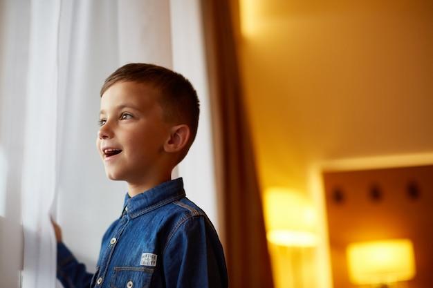 Маленький мальчик у окна в помещении
