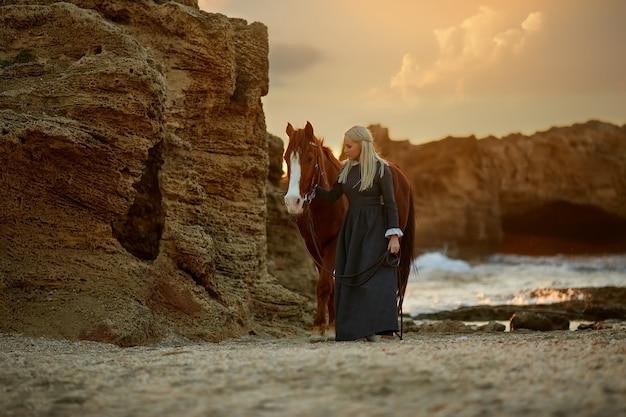 Женщина с лошадью на скалистом берегу моря
