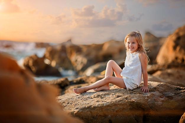 Красивая маленькая девочка сидит на скале и смотрит вдаль