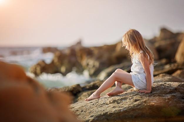 Маленькая девочка в платье сидит на пляже у моря на закате