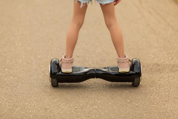 Девушка катается на гироскутере летом по площади