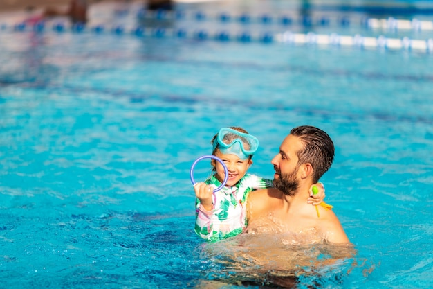 Папа учит маленькую дочь плавать в бассейне