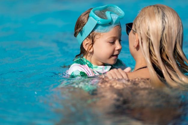 母と娘がプールで泳いで