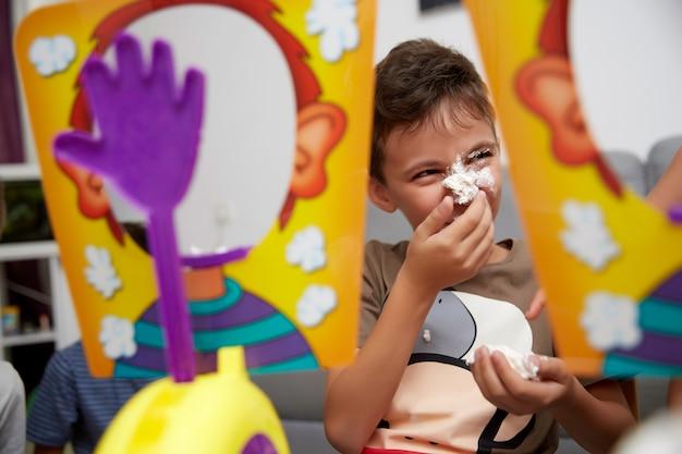 Мальчик десяти лет играет в забавную игру со сладкими сливками, кремом в лицо