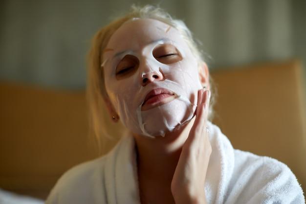顔シートマスクを作る若いブロンドの女性。美容とスキンケアのコンセプト