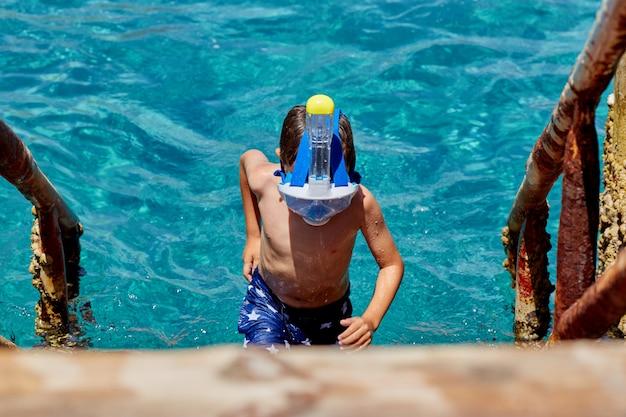 シュノーケルマスクチューバと海でシュノーケルを持つ男。シュノーケリング、水泳、休暇。