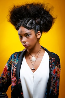 孤立した黄色の壁に彼女の鼻にイヤリングと夏の花ブラウスを着ている若いラテン系アメリカ人。