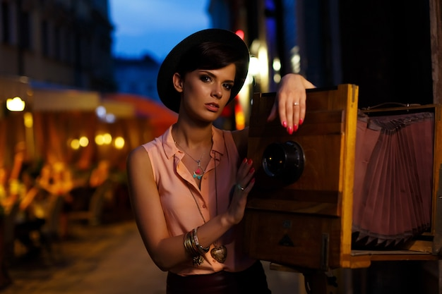 カメラでビンテージ写真で美しい少女と夏の街を歩く